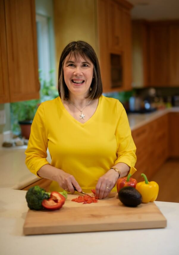Cindy Sullivan in a yellow shirt chopping vegetables