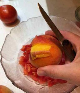 Small section of peach peel is peeled away with knife and bowl in the picture.