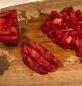 half, sliced and chopped seeded tomatoes on a cutting board