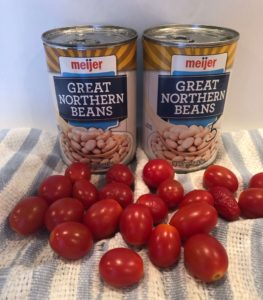 Great Northern beans in cans & tomatoes on a blue and white striped vegetable towel