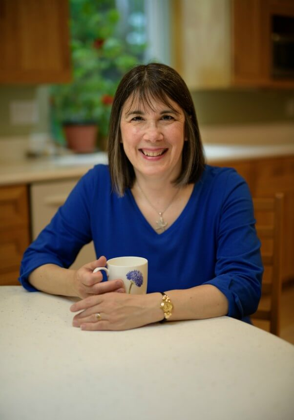 Cindy Sullivan sitting at kitchen table with a cup of tea