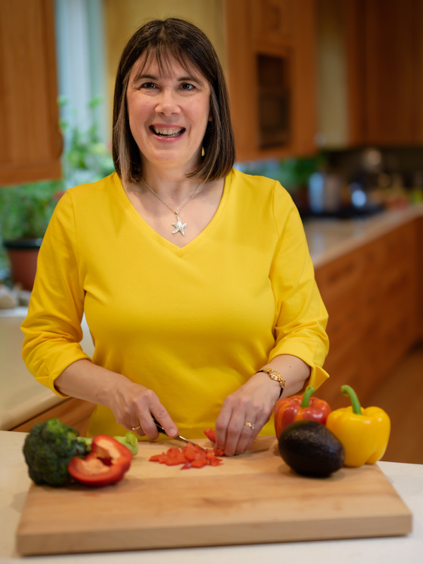 Cindy in yellow shirt lookin up and smiling with vegetables on cutting board