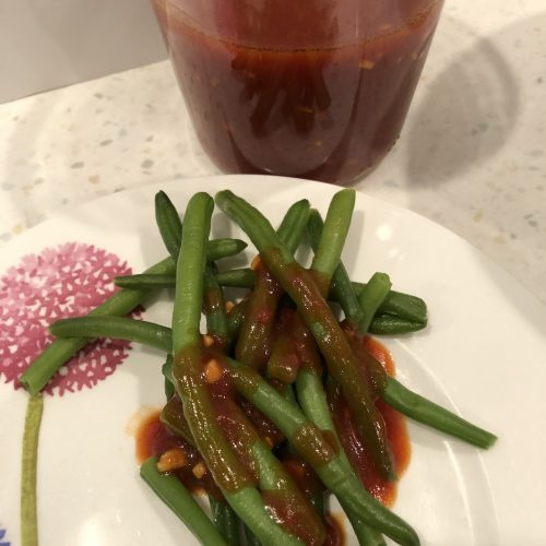 fermented ketchup dressing over green beans with the container of dressing behind the plate with beans