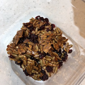 maple roasted pumpkin seeds in clear plastic container