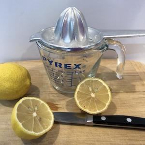 2 cut lemons on cutting board, lemon reamer glass measuring cup
