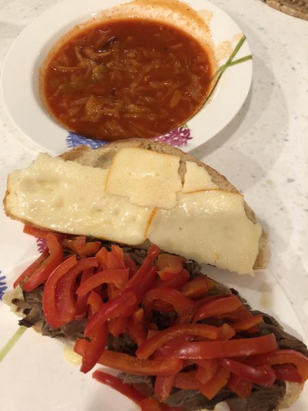 Homemade Philly cheesesteak sandwich and a bowl of cabbage soup