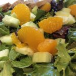 mandarin oranges on top of tossed salad with avocado and cucumber