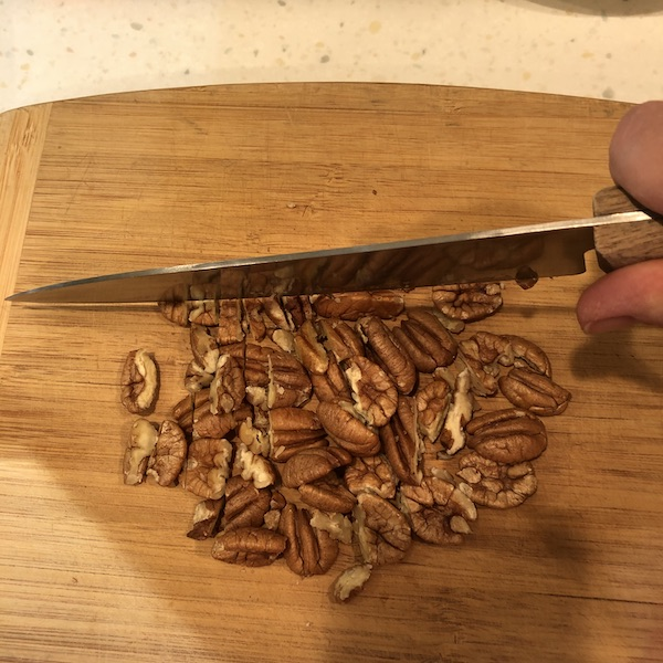 Chopping pecans on cutting board with a cooks knife