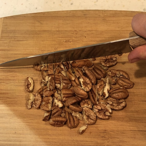 chopping pecans with a cook's knife on wooden cutting board