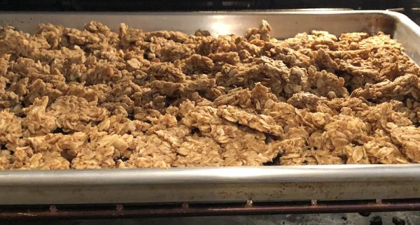Big chunks of nut free, gluten free granola on a rimmed baking sheet in the oven