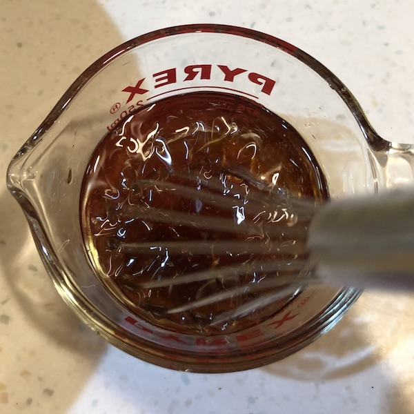whisking liquid ingredients in a glass measuring cup