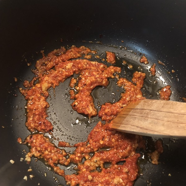 garlic, ginger & red curry paste sauteing in pan.
