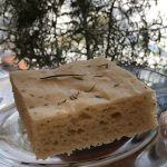 Focaccia on a glass plate with rosemary plant in background