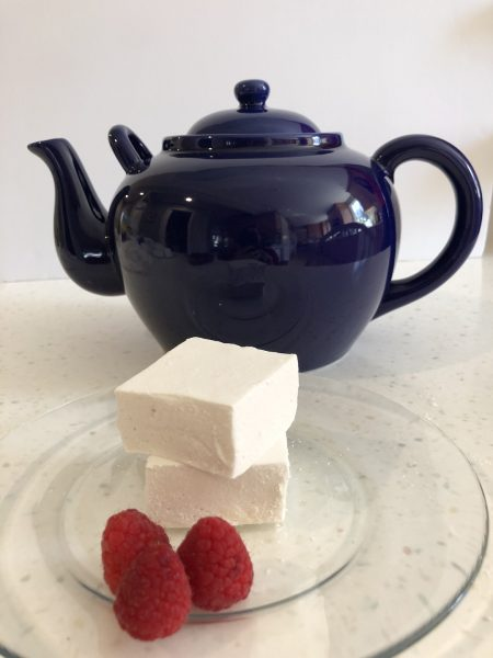 two marshmallows on a clear plate with three raspberries and a blue teapot in background