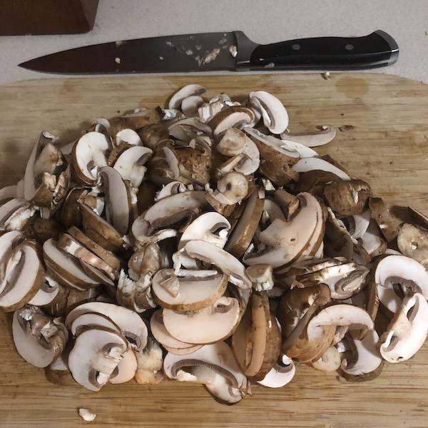 sliced mushrooms & knife on cutting board