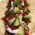 Taco Meat and Beans with avocado, tomato & sour cream on a flour tortilla