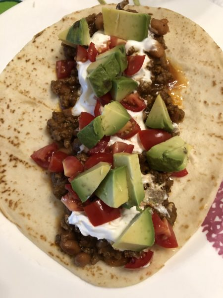 Taco Meat & Beans in a flour tortilla topped with avocado, tomatoes, sour cream