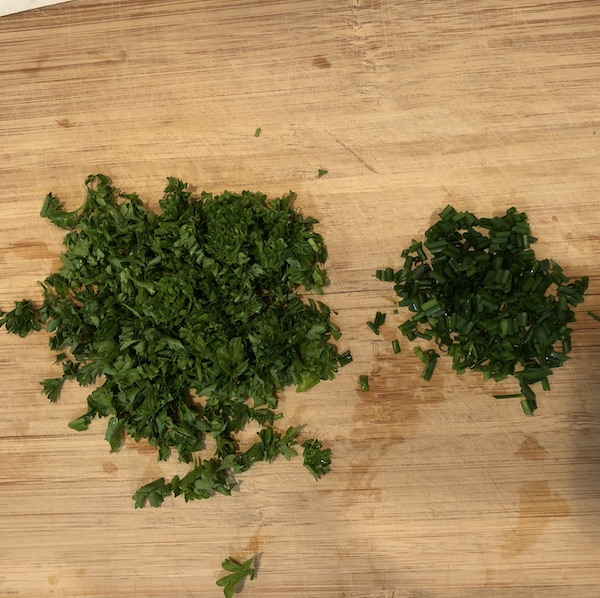 Chopped parsley and chives on a wooden cutting board.