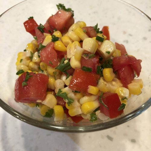 Fresh Corn Tomato Salad in a clear glass bowl on a white counter.