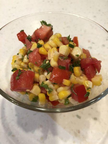 Fresh corn tomato salad in a small glass bowl.