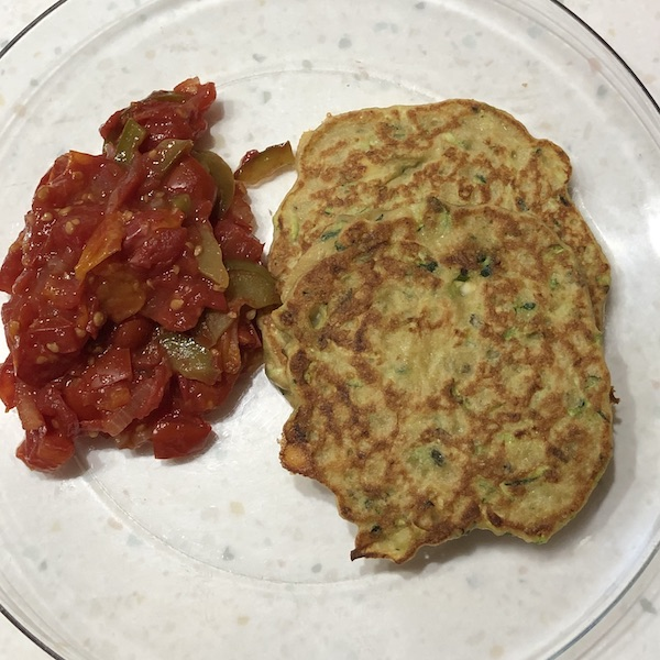 Tomatoes, onions & peppers on a clear plate with 2 zucchini pancakes.